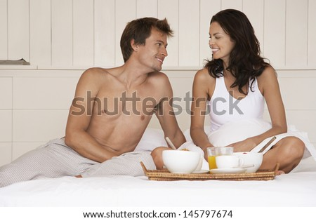 Happy romantic young couple having breakfast in bed - stock photo
