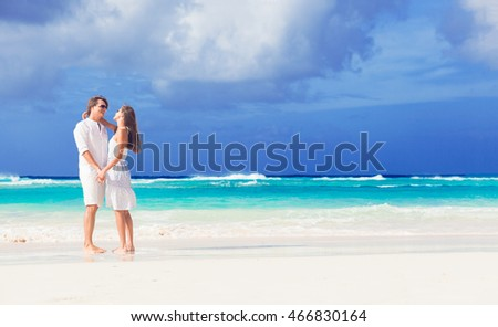 happy romantic young couple walking at the beach
