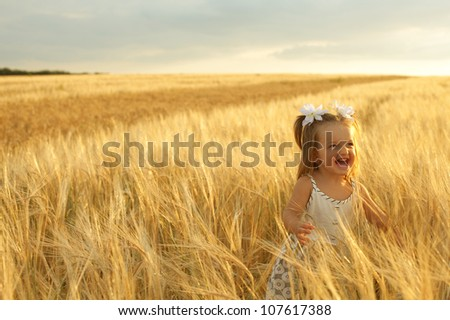 happy running girl on a wheat field in the sunlight - stock photo