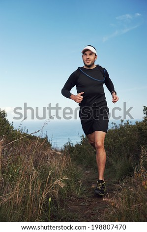 happy running man on trail exercising outdoors - stock photo