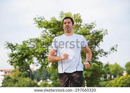 Happy running man outdoors - stock photo