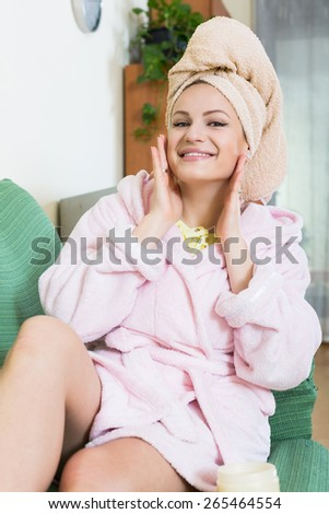 Happy russian blonde with face pack relaxing on sofa indoors - stock photo