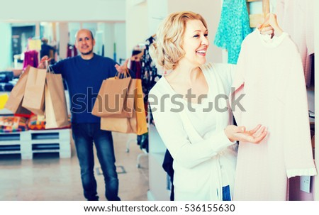 happy russian elderly wife buying dress at apparel store, man is bored