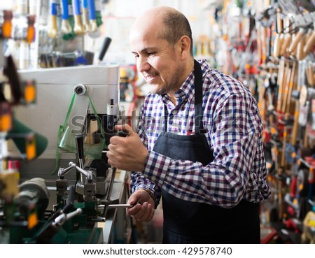 happy russian senior professional with different types of keys in locksmith - stock photo