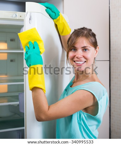 Happy russian woman cleaning empty refrigerator indoors