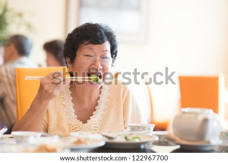 Happy 60s Senior Asian Woman eating vegetable at restaurant - stock photo
