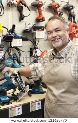 Happy salesperson with electric saw in hardware store - stock photo