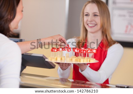 Happy saleswoman offering small cheese blocks with Swiss flag to customer in grocery store - stock photo