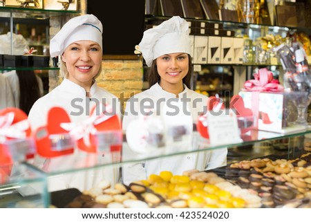 Happy saleswomen with delicious chocolate and confectionery at display . Selective focus