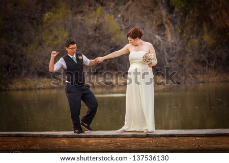 Happy same sex couple dancing on dock over lake - stock photo