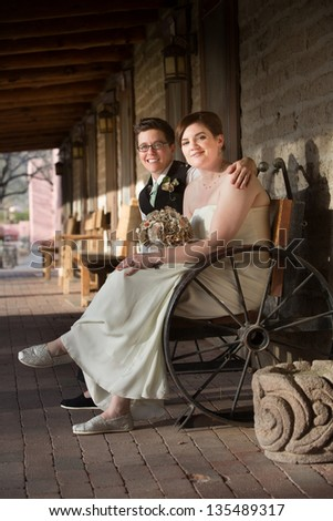 Happy same sex couple in wedding on antique bench