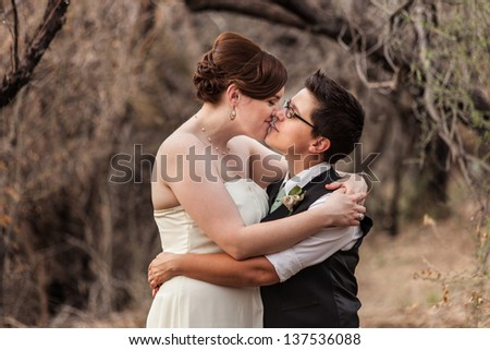 Happy same sex newlyweds kissing in the woods - stock photo