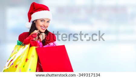 Happy Santa Christmas woman with bags over blue background.