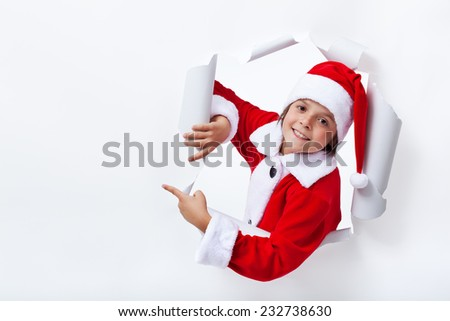 Happy Santa Claus costume boy pointing to copy space - christmas advertising - stock photo