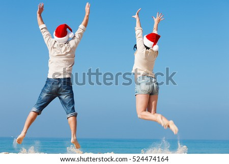 Happy Santa Claus couple jumping on the beach