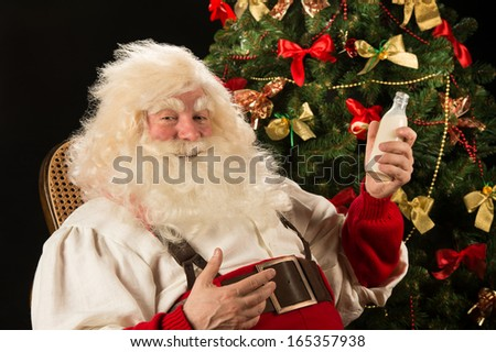Happy Santa Claus drinking milk from glass bottle against Christmas Tree at home.