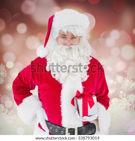 Happy santa claus holding a gift against glowing christmas background - stock photo