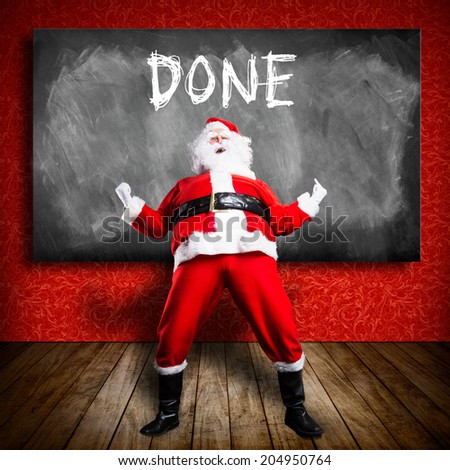 "happy Santa Claus in front of a blackboard with the text ""done"" - stock photo"