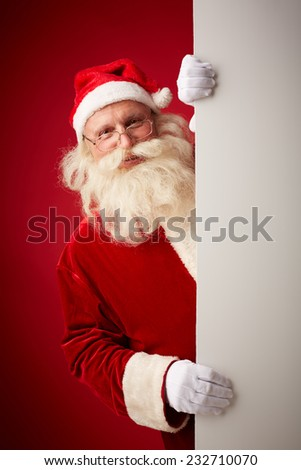 Happy Santa Claus looking at camera out of billboard - stock photo