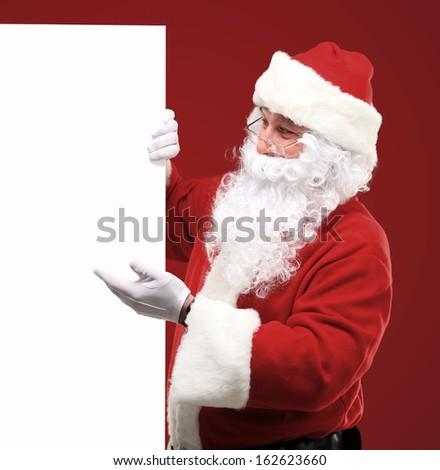 Happy Santa Claus looking out from behind the blank sign isolated on red background with copy space  - stock photo