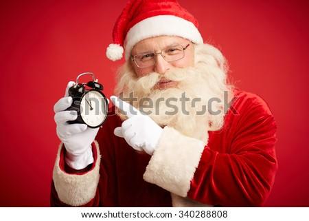 Happy Santa Claus showing at alarm-clock and looking at camera - stock photo