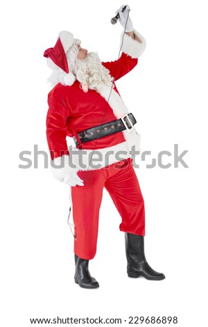 Happy santa claus singing with microphone on white background - stock photo