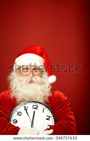 Happy Santa Claus with clock showing five minutes to midnight - stock photo