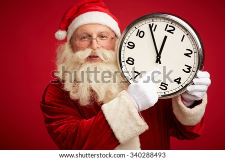 Happy Santa holding clock showing five minutes to twelve