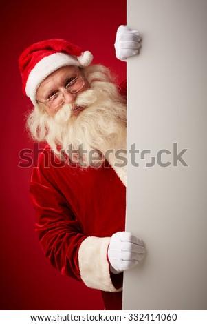 Happy Santa looking at camera out of blank billboard - stock photo