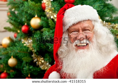 Happy santa portrait with a Christmas tree behind indoors - stock photo