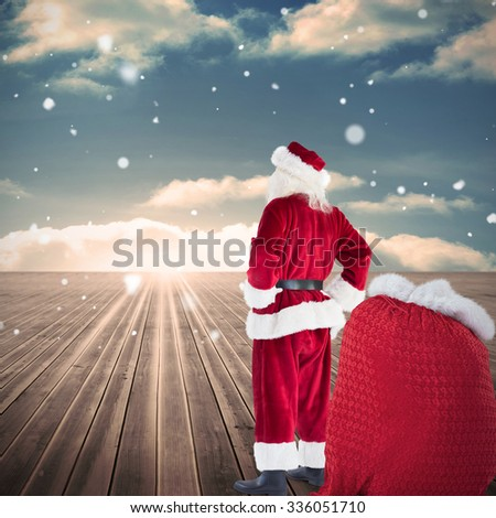 Happy santa with sack of gifts against wooden planks leading to blue sky - stock photo