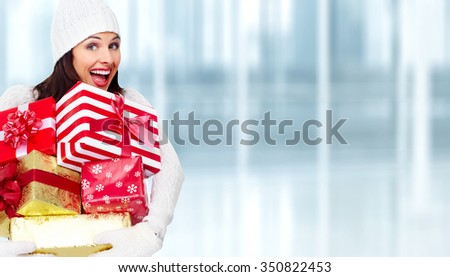 Happy Santa woman with Christmas gift over shopping mall background.