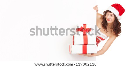 Happy santa woman with gift boxes and blank board isolated on white. Smiling model in santa hat at studio with gift. Christmas, xmas, winter, happiness concept. Santa girl hold gift box with red tape