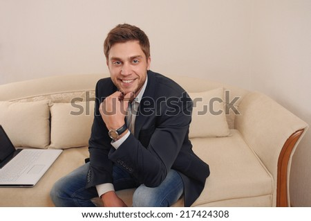 happy satisfied successful young man working on laptop at home on the sofa - stock photo
