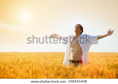Happy, satisfied young man with arms outstretched standing in the wheat field.Copy space, sunset, flare light, summer season - stock photo