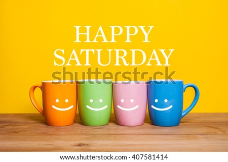 Happy saturday word.cups of coffee and stand together on yellow background with smile face on cup. - stock photo