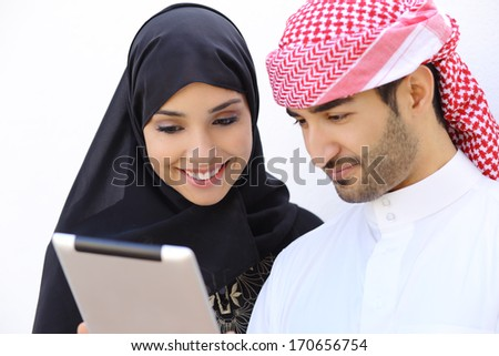 Happy saudi arab couple looking a tablet together on a white wall background
