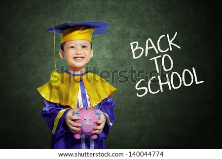 Happy scholar dressed toddler carrying a piggy bank - stock photo
