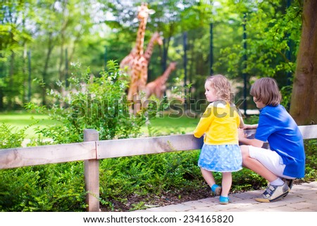 Happy school boy and his toddler sister cute little girl with curly hair wearing a dress having fun together in a zoo watching giraffes and other animals on a day trip during summer vacation  - stock photo