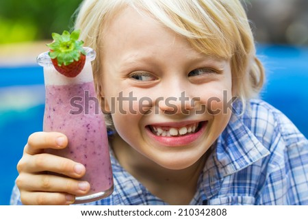 Happy school boy drinking a healthy smoothie as a snack - stock photo