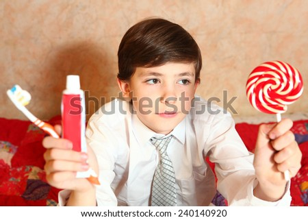 happy school boy make choice between candy and toothbrush - stock photo