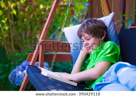 Happy school boy reading a book in the backyard. Child relaxing in a garden swing with books. Kids read during summer vacation. Children studying. Teenager kid doing homework outdoors. - stock photo