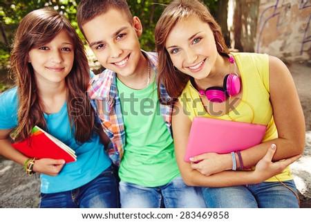 Happy school friends looking at camera - stock photo