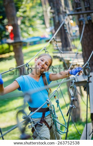 Happy school girl enjoying activity in a climbing adventure park on a summer day - stock photo