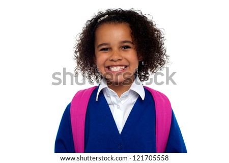 Happy school going girl. Beautiful African student in uniform with backpack smiling at you. - stock photo