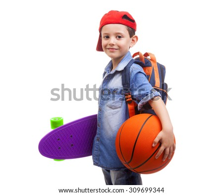 Happy school kid holding a skateboard and a basketball on white background - stock photo