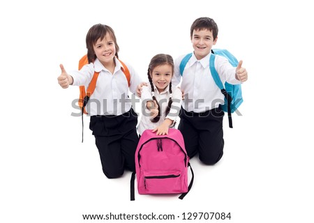 Happy school kids giving thumbs up sign - isolated - stock photo