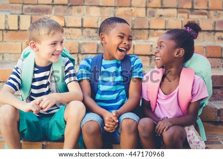 Happy school kids sitting together on staircase at school - stock photo