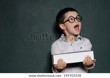 Happy schoolboy. Cheerful little schoolboy in glasses holding a book and laughing while standing in front of blackboard - stock photo