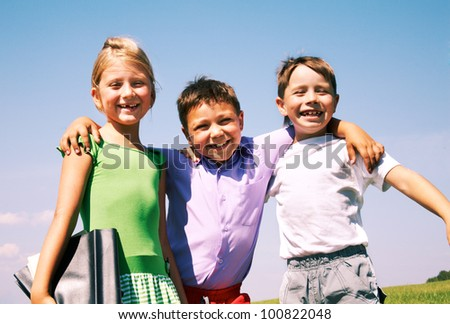 Happy schoolboy embracing his friends outdoor - stock photo